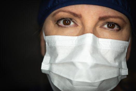 Female Doctor or Nurse Wearing Medical Face Mask on Dark Background.