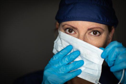 Female Doctor or Nurse Wearing Surgical Gloves Putting On Medical Face Mask.