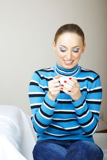Smiling woman indoors in striped sweater holding cup with tea or coffee
