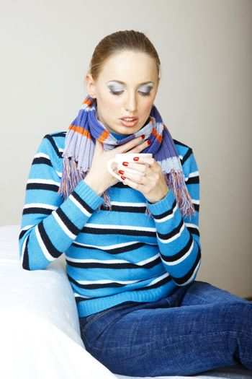 Sick woman drinking hot tea. Indoors photo
