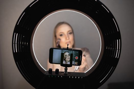 Beauty blogger recording makeup tutorial video at home