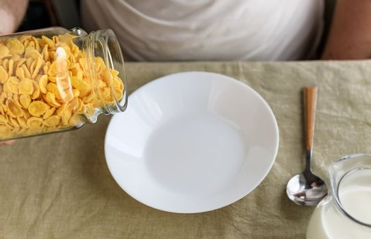 A cropped man sprinkles cornflakes in a white plate on a plain rough tablecloth. Close-up. Top view. Selective focus. Concept, simple fast american healthy breakfast