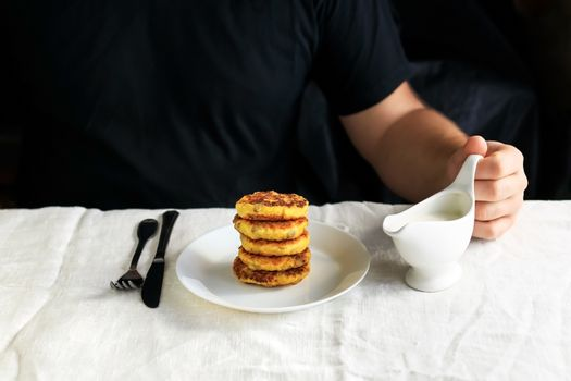 A circumcised man in a black T-shirt holds a white gravy boat in his hands and pours the curd cheesecakes on a plain white tablecloth with sour cream sauce. Concept, simple healthy breakfast.