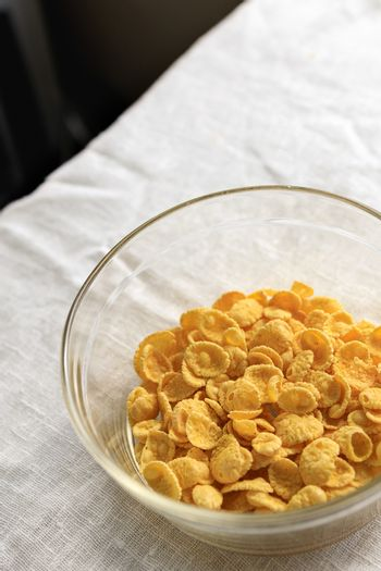 Cornflakes in a transparent glass plate on a light rustic tablecloth table. Copy space.
