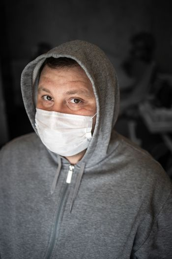Young adult male with a gray hood in a medical mask. Restless serious look straight. Dark gray background. Selective focus. Concept, prevention of viral flu, coronavirus.