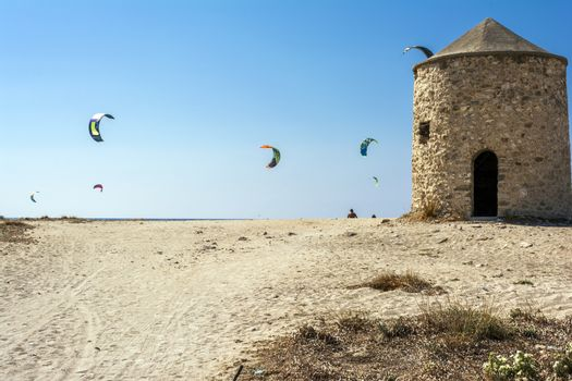 Agios Ioannis beach in Lefkas island Greece. Colorful power kites span across the sky from kite-surfers. Agios Ioannis is home to some old windmills.