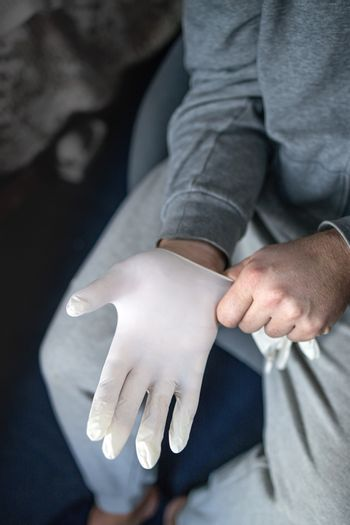 Man in gray clothes putting on medical latex gloves. The concept, prevention and protection against coronovirus infection