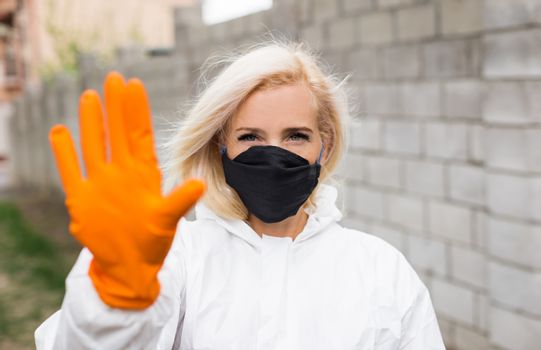 Woman in black mask, white protective suit and gloves making sigh stop