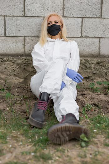 Woman in black mask, white protective suit and gloves sitting against wall