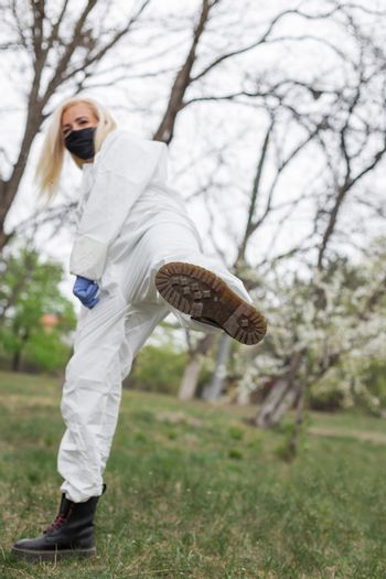 Woman in black mask, white protective suit with leg up