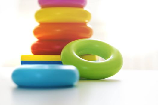 Colorful plastic rings on a white background to be stacked in a tower. Toy for newborns.