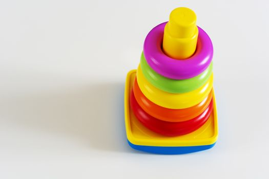 Plastic rings of various colors are stacked in a yellow plastic tower. Educational game for infants to develop their skills and creativity