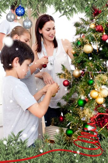 Happy children and parents decorating a Christmas tree against snow falling