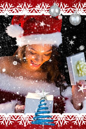 Pretty brunette in santa outfit opening gift against snow falling