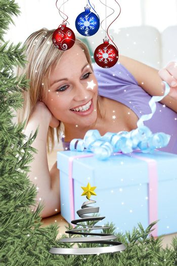 Cheerful blond woman holding a present lying on the floor against twinkling stars