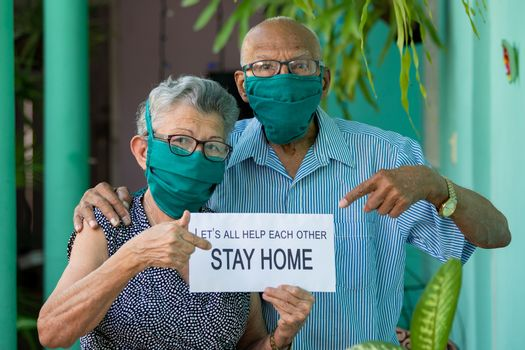 An elderly couple, both wearing face mask and glasses and holding an stay home sing