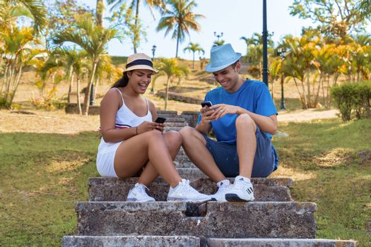 Couple of smiling young people sitting, each with a cellphone in their hands