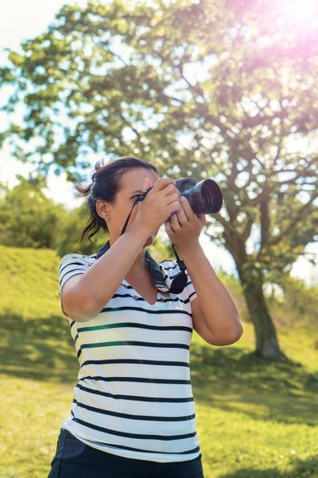 A black hair standing woman with a camera taking pictures
