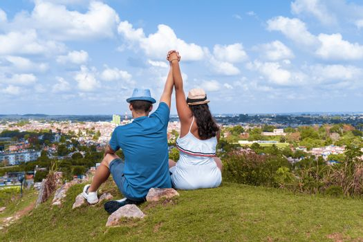 A couple of young people wearing hat with their arms up sitting on the floor looking towards a city from a hill