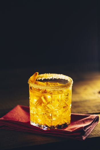 Glass of the cocktail negroni on a old wooden board. Drink with
