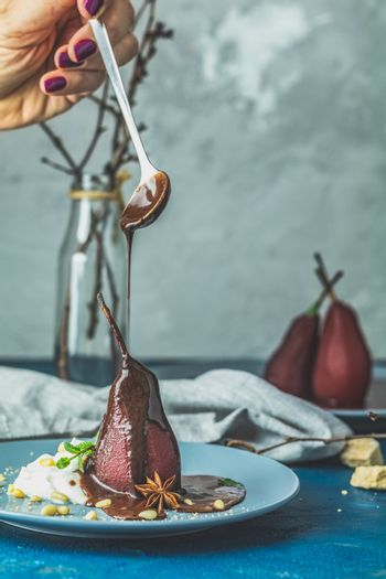 Chocolate sauce pours from a spoon on red pears in wine