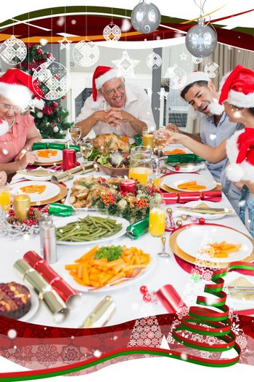 Happy family in santas hats enjoying Christmas dinner against snow falling