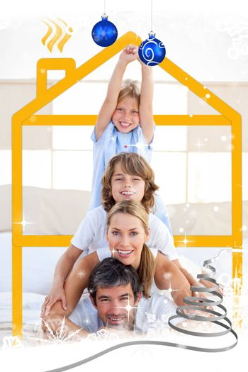 Family having fun with yellow drawing house against snow falling