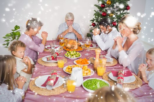 Composite image of Family saying grace before christmas dinner against snow falling