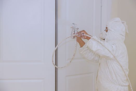 Man painting door with white colour using spray paint gun hand the tool the spray of paint