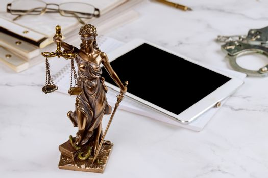 Lawyer Statue of Justice with scales lawyers symbols office working on a digital tablet