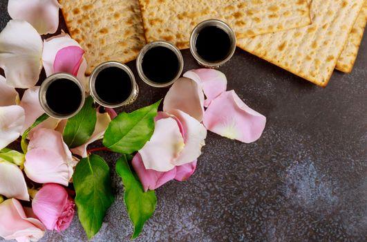 Matzoh passover jewish holiday celebration matzoh with kiddush four cup of red kosher wine on fresh pink rose flower