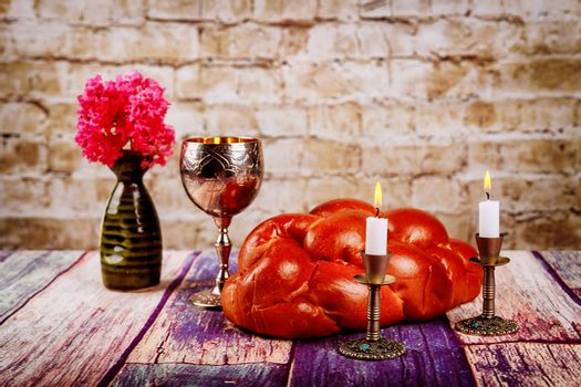 Shabbat candles in candlesticks of loaves challah for Shabbat wine in a kiddush cup with flowers