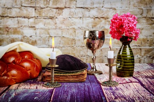 Shabbat candles in candlesticks of loaves challah for Shabbat wine in a cup with flowers
