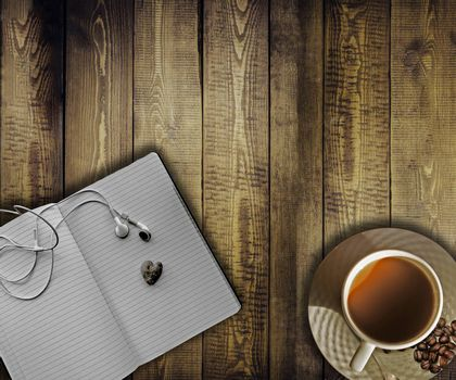Wooden table background with coffee cup, notepad and music helmets. Blank space for text.