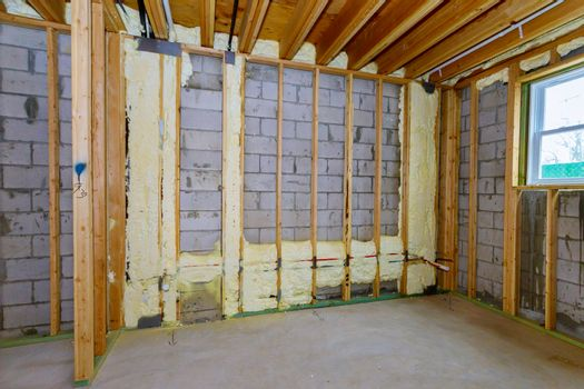 New wooden house in foam for insulation the wall of a basement unfinished under construction