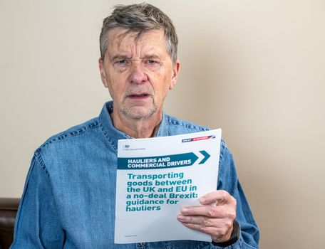 Senior caucasian truck driver reading Brexit no deal rules for exporting