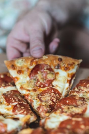 Cropped man takes a piece of pizza with his hand. Selective focus, blur, closeup.