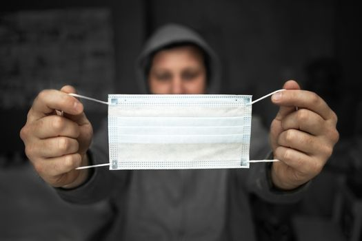 A man in a gray hood holds a medical mask in front of him on a dark background. Selective focus. copy space. The concept of prevention and protection against seasonal viral flu and coronovirus infection
