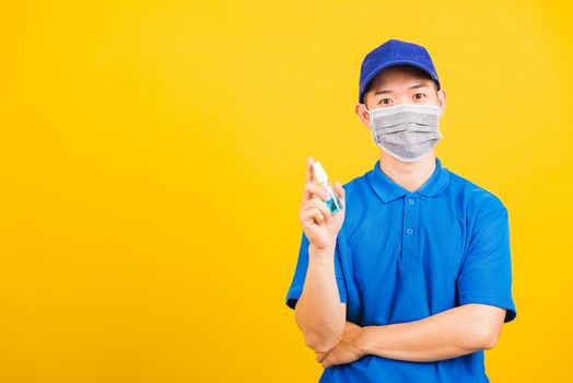 Asian young handsome delivery man wearing face mask protective germ virus and show alcohol sanitizing sprays on hand, studio shot isolated on yellow background, medical outbreak coronavirus COVID-19