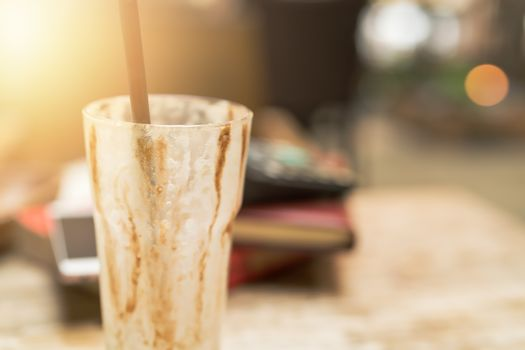 empty cup of iced mocha coffee on wooden table background.