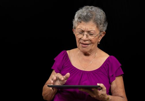 Elder woman wearing glasses with a tablet
