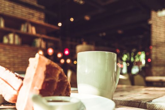Hot mocha coffee in white cup and blurred waffle on the wooden t