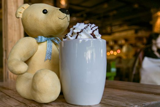 a light brown cute bear with a hot mocha coffee with whipping cr