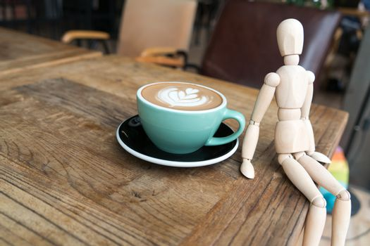 Hot mocha coffee or capuchino in the green cup with a wood man s