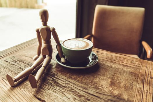 a wood man sitting and touch the hot mocha coffee or capuchino i