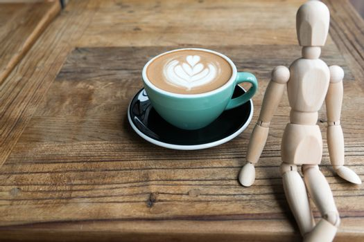 Hot mocha coffee or capuchino in the green cup on the wooden tab
