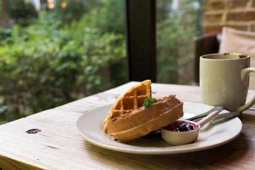 2 pieces of waffle with a white cup of coffee on the wooden tabl