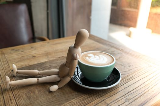 Hot mocha coffee or capuchino in the green cup lean by wood man