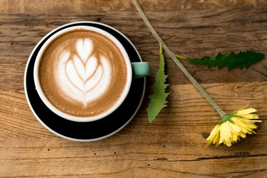 Hot mocha coffee or capuchino with heart pattern and yellow flow