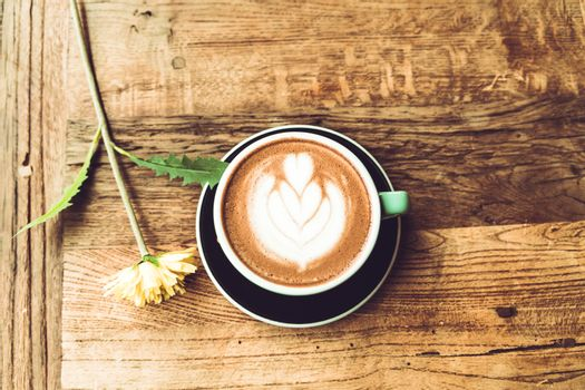 Hot mocha coffee or capuchino in the green cup with heart patter